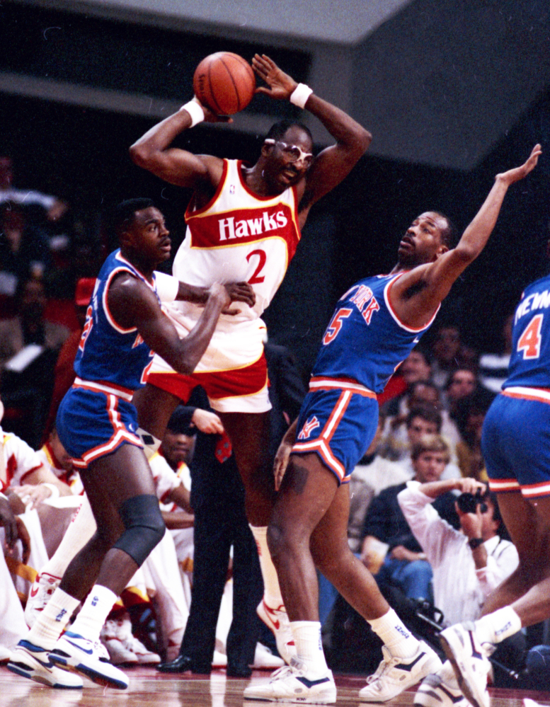 In this Dec. 1988 file photo, Atlanta Hawks' Moses Malone, center, is double-teamed by New York Knicks' Gerald Wilkins, left, and Eddie Wilkins during an NBA basketball game, in Atlanta. Malone, a three-time NBA MVP and one of basketball's most ferocious rebounders, died Sunday the Philadelphia 76ers said Sunday. He was 60.