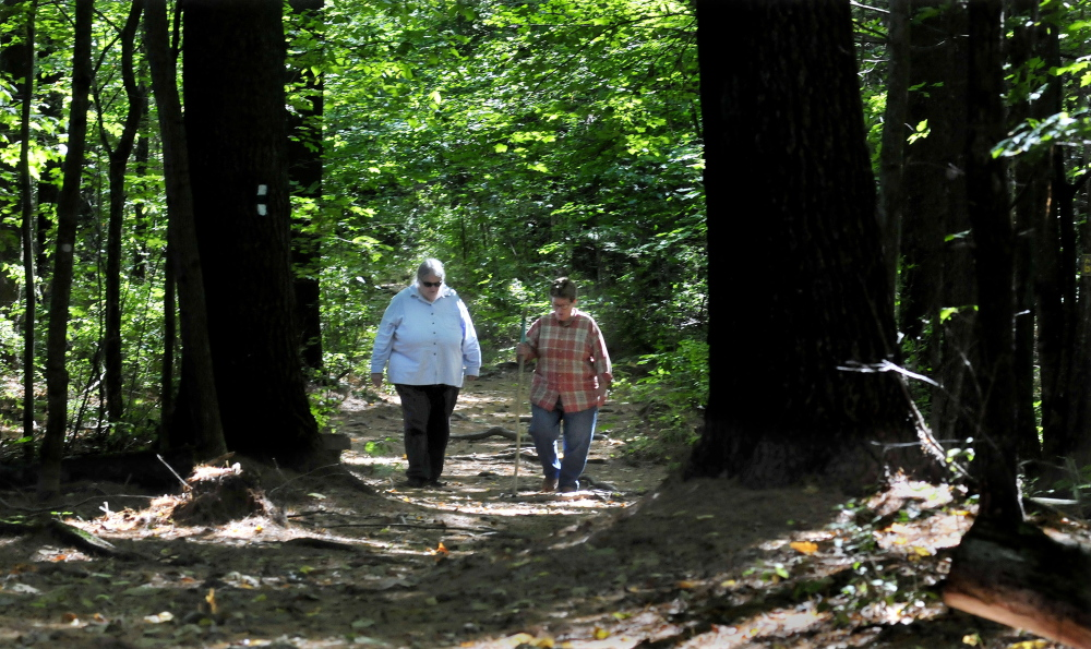 Deborah Staber, left, director of the L.C. Bates Museum in Hinckley, and Melissa Bastien, walk along the Dartmouth Trail behind the museum on Monday. This Saturday is the 100th anniversary of the trail and officials hope 100 hikers show up to celebrate.