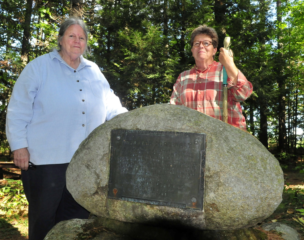 Deborah Staber, left, of the L.C. Bates Museum in Hinckley, and Melissa Bastien, stop along the nearby Dartmouth yrail beside the Roosevelt monument on Monday.
