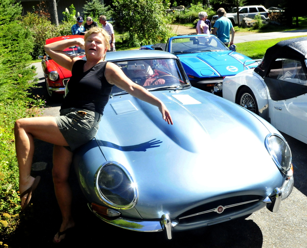 Nona Fuller of Nova Scotia poses with her 1966 Jaguar E-Series sports car at a stop in North Belgrade on Tuesday.  Fuller and others with the BATANS club, British Automobile Touring Association Nova Scotia, were driving their British cars from Nova Scotia to Vermont.