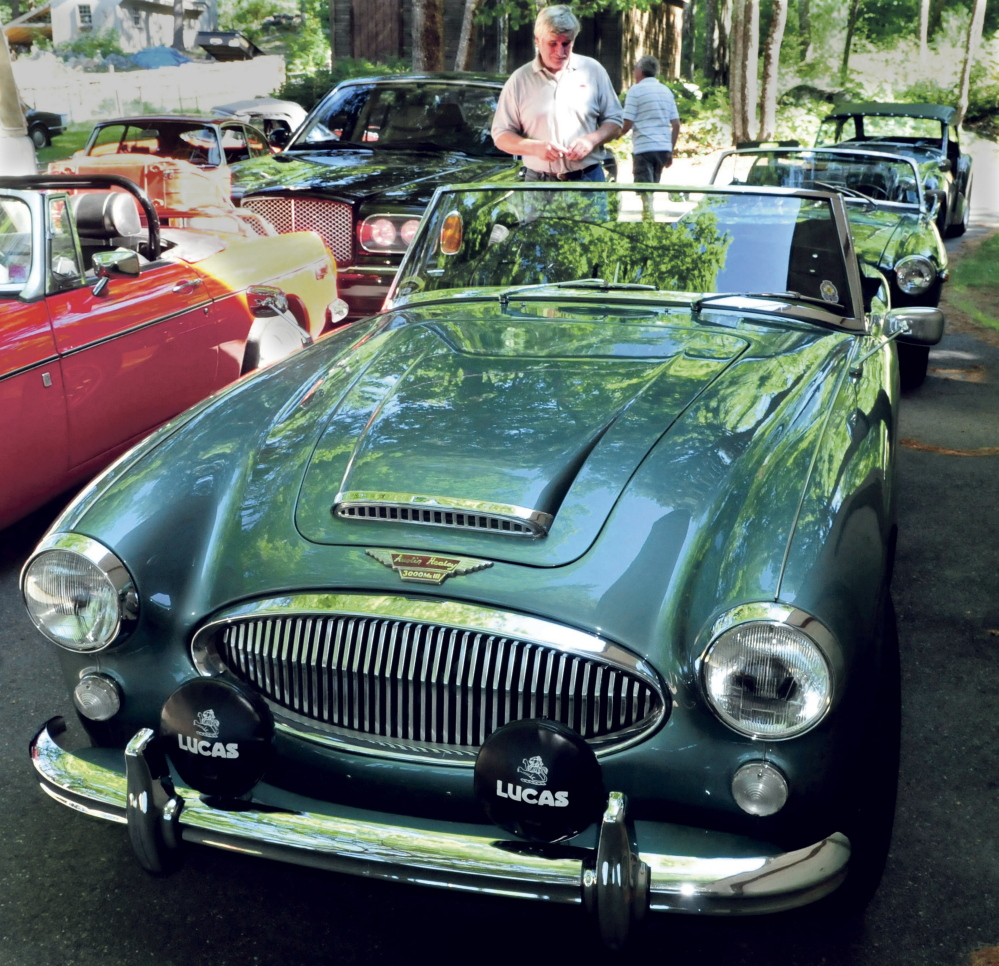 Ray Morrow of Smithfield admires an Austin Healey 3000 at the home of Steve and Janet Towle in North Belgrade on Tuesday. The car was one of a caravan of British-made cars on their way from Nova Scotia to Stowe, Vermont, for the British Invasion car show.