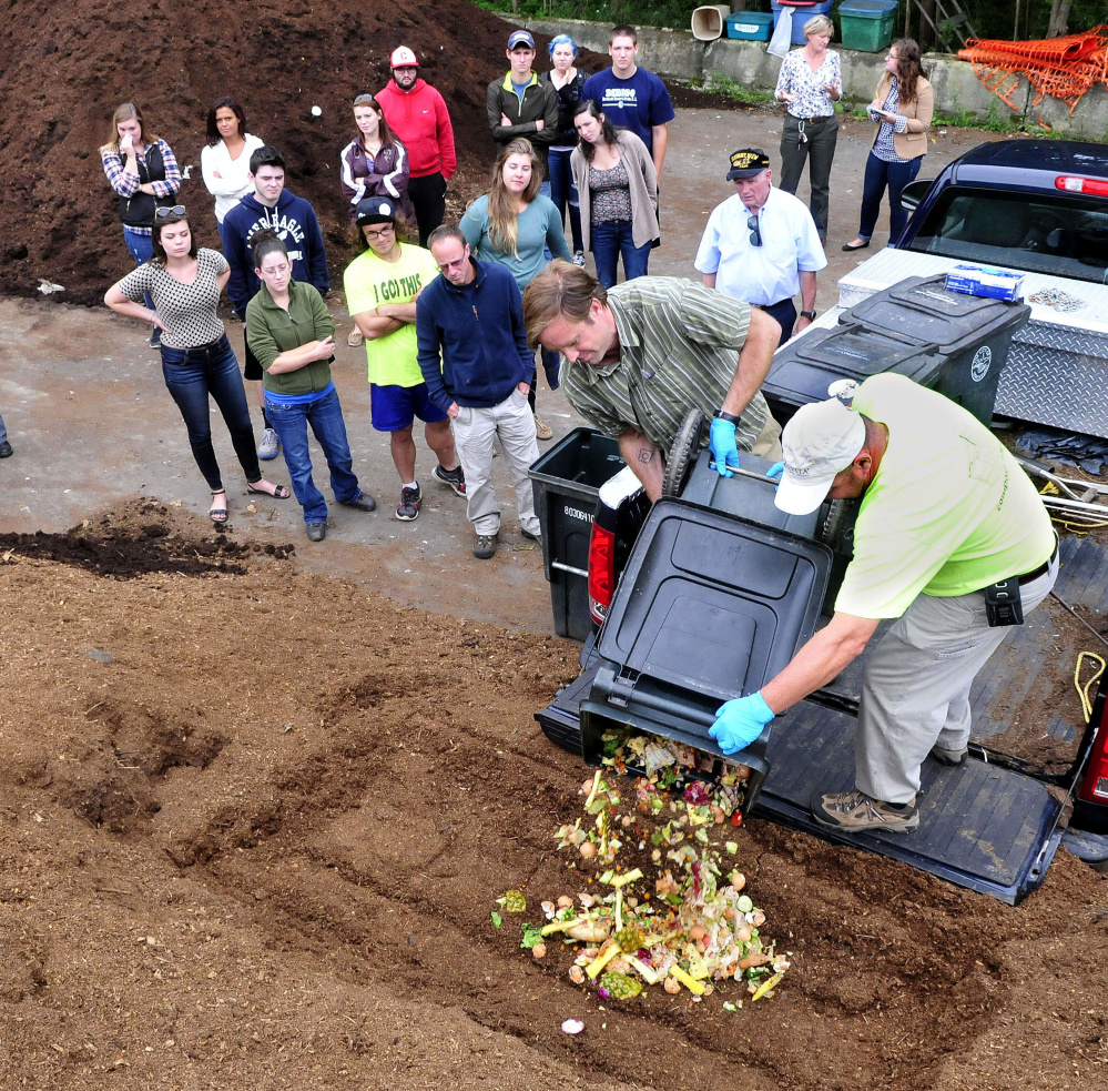 Staff photo by David Leaming University of Maine in Farmington professor Luke Kellett, left, and Mark King of the DEP pour out food waste from campus onto a pile of composting material as students watch at the Farmington Compost Cooperative site on Tuesday.