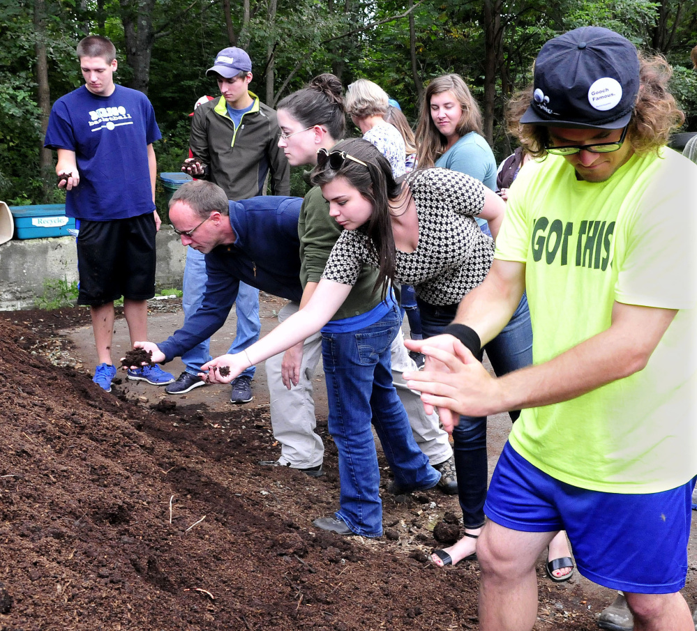 University of Maine in Farmington students feel and smell compost material made from food and farm waste at the Farmington Compost Cooperative site on Tuesday. Student Glenn Lumbert, right, claps the material off his hands.