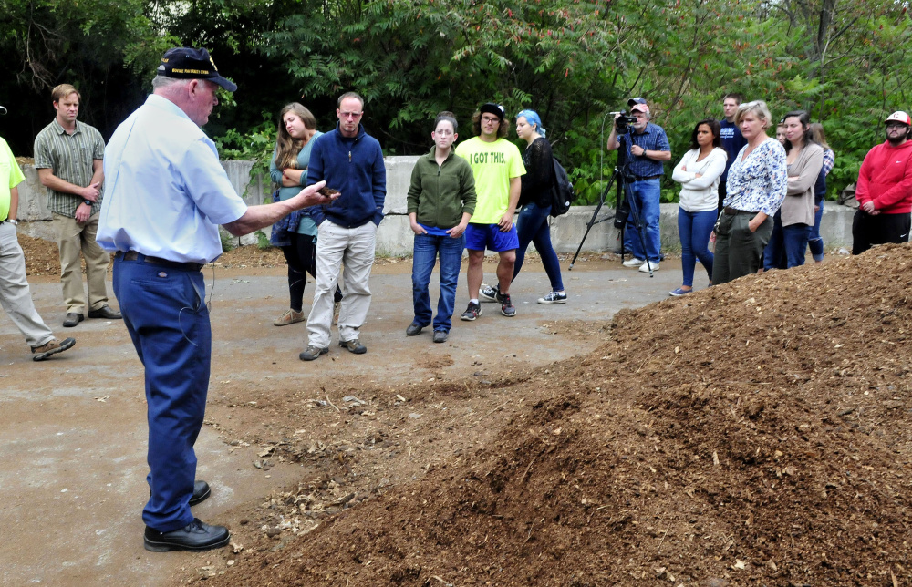 Staff photo by David Leaming Farmington Compost Cooperative volunteer Tom Eastler explains how bacteria breaking down food and farm waste produces heat while making nutrient rich material to UMF students Tuesday.
