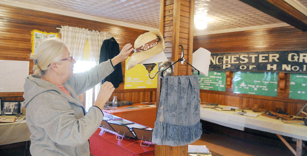 Linda Cobb arranges a bonnet Thursday at the Manchester Grange in preparation for a display by the Manchester Historical Society on Sunday.