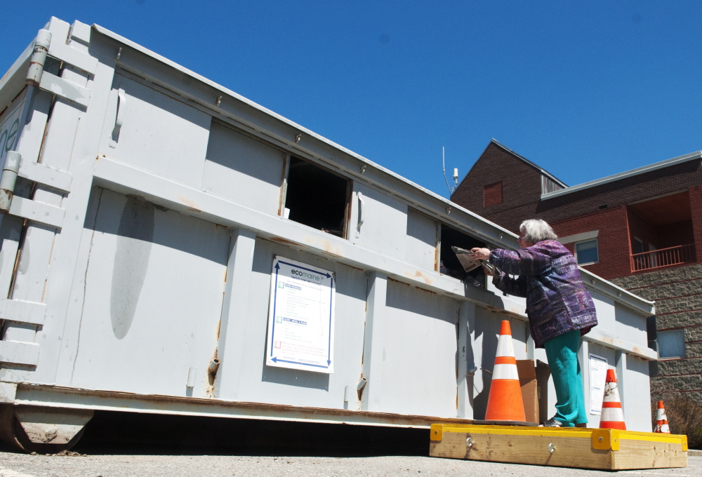 Laurie Southard tosses recyclables into the container in the back lot of Augusta City Center on May 2 in Augusta. The containers for the city's recycling program are available for Augusta residents only.