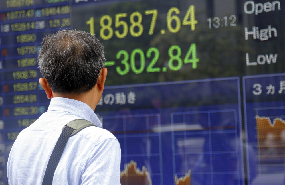 A man looks at an electronic stock indicator of a securities firm in Tokyo on Tuesday. The Associated Press