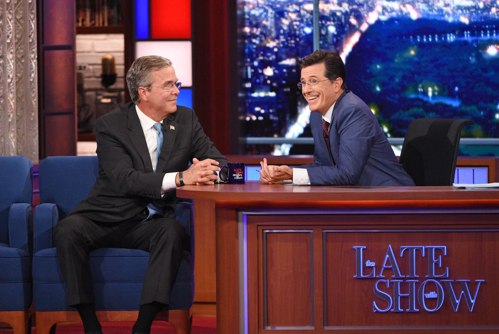 """Stephen Colbert talks with Republican presidential candidate Jeb Bush during the premiere episode of """"The Late Show"""" on Tuesday in New York. Bush and actor George Clooney were the guests for Colbert's debut."""