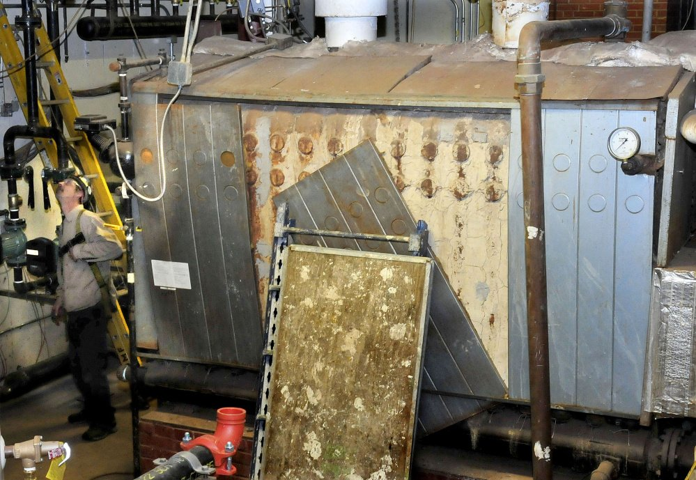 One of two large oil furnaces will soon be replaced with a single, small heat exchanger for the biomass heating system in Scott Hall dormitory at the University of Maine at Farmington.