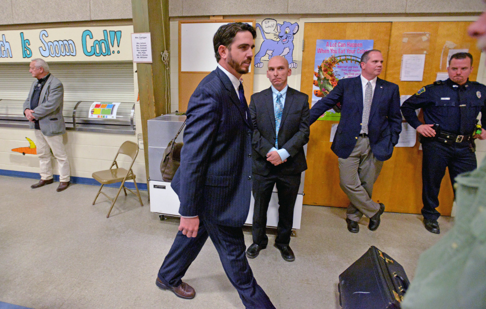 Waterville Senior High School principal, Don Reiter, leaves a public hearing Tuesday at George J. Mitchell School in Waterville. Waterville police Detective Sgt. Bill Bonney, with hands folded, looks on.