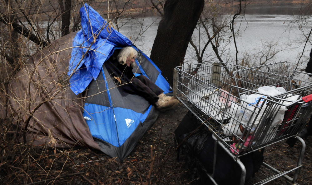 Homeless man Vaughan Orchard climbs out of his tent where he lives along the Kennebec River in Waterville on Tuesday.