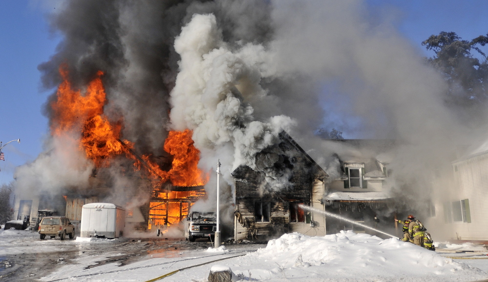 Waterville firefighters battle a blaze at 160 Drummond Ave. in Waterville on Dec. 25, 2013. A body was found outside the same house Saturday, almost two years to the day after the fire.
