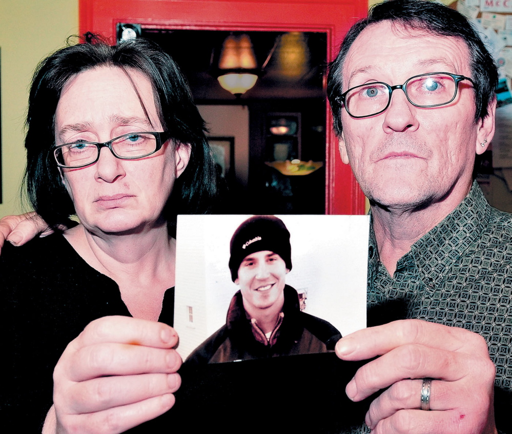Lorna and Michael Smilek hold a 2006 photograph of Michael's son Justin Crowley-Smilek, who was shot and killed after he confronted Farmington police.
