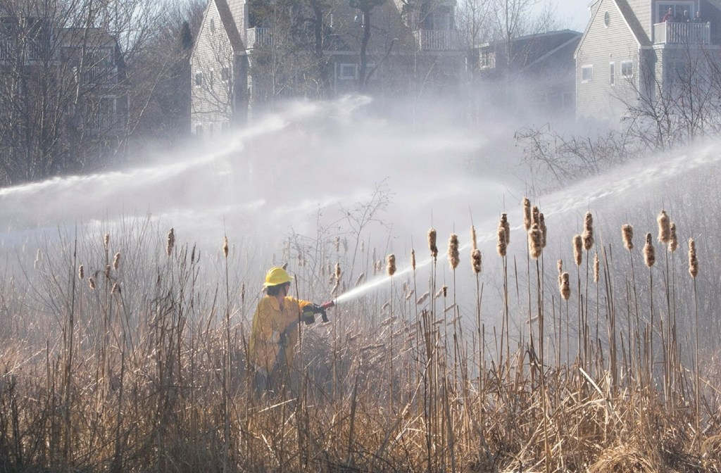 Firefighters battle the four-alarm brush fire that Ricky Plummer is charged with setting in April in Old Orchard Beach.