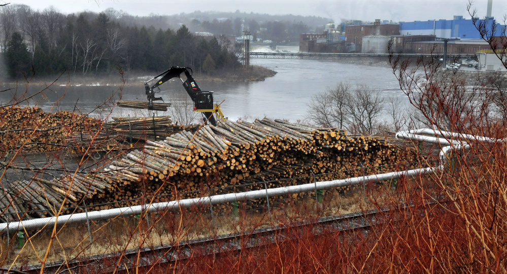 A worker unloads logs March 15 in a wood yard that were to be used to make paper at the Madison Paper Industries mill in Madison, background. Madison Paper is scheduled to cease production the week of May 28 and keep workers on until June 12 for maintenance, equipment shutdown and cleaning.