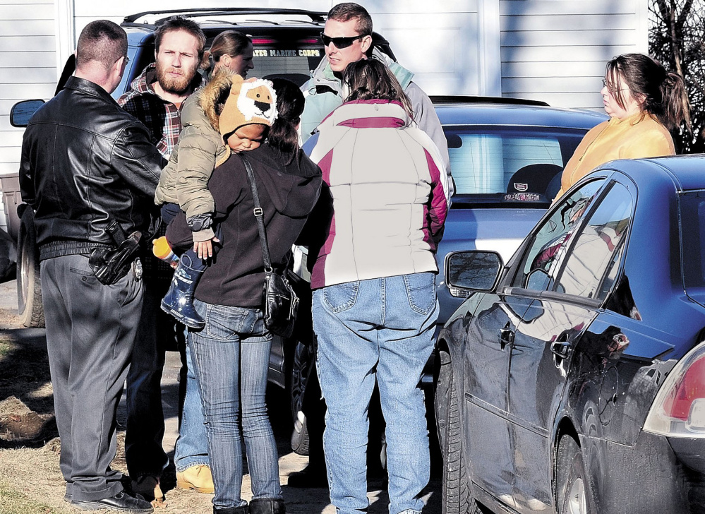 """Maine State Police Detective Christopher Tupper, left, and Waterville Police Detective Lincoln Ryder, at right, speak with Justin DiPietro at his home on Violette Avenue in Waterville on Dec. 18, 2011, the day after he reported his daughter, Ayla Reynolds, missing. Beside DiPietro is his then-girlfriend, Courtney Roberts, holding a baby; his mother, Phoebe DiPietro; and sister, Elisha DiPietro, at right. Elisha DiPietro told the TV show """"Crime Watch Daily"""" that they believe Ayla is still alive """"out there somewhere."""" Ayla's mother's family wants Justin and Elisha DiPietro and Roberts charged in the toddler's death and is bringing a civil suit against them."""