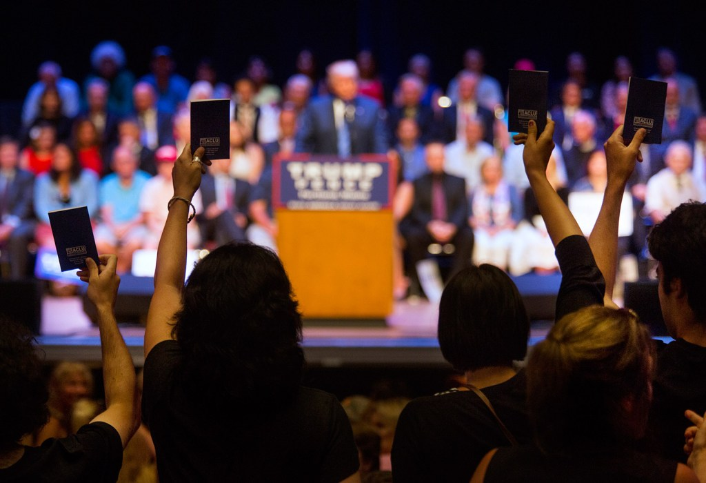Protesters hold up pocket Constitutions during Thursday's rally by Donald Trump's campaign at Merrill Auditorium.