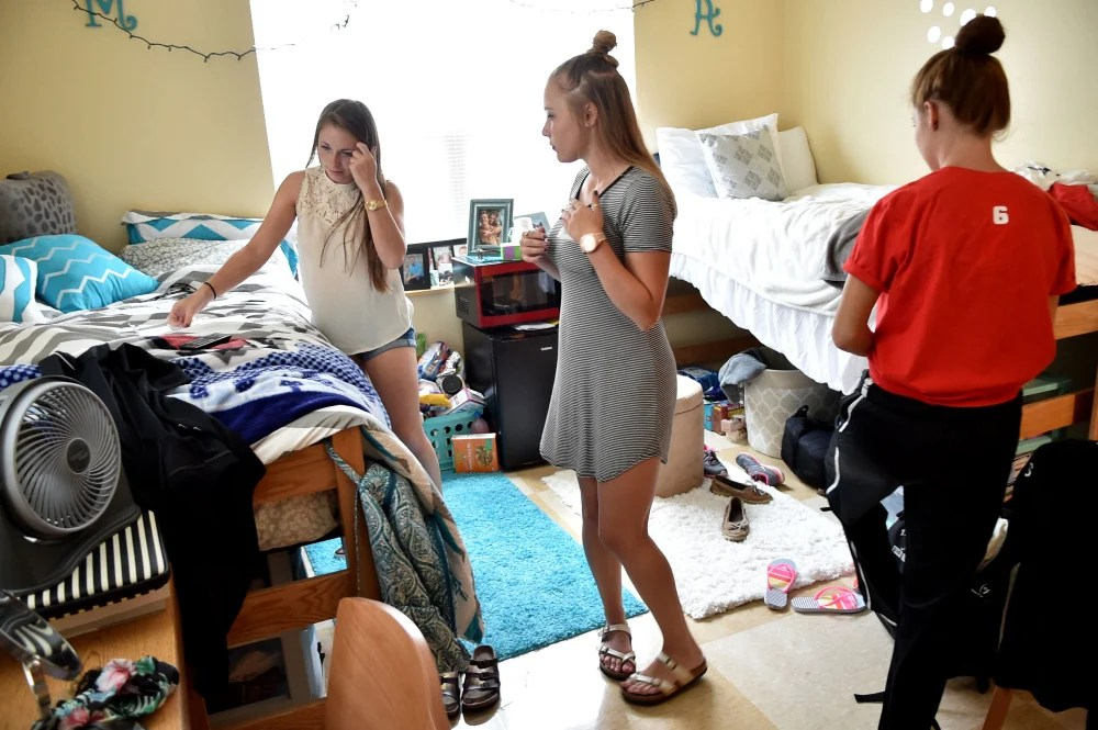 Mackenzie Carlow, left, settles in to her dormitory room Friday with her roommates Taylor Peno, center, and Ashlyn Parker at Thomas College in Waterville.