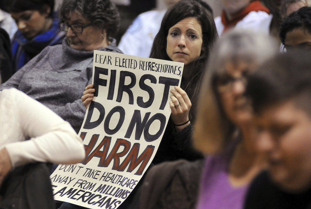 Amy Kuiken, 34, of Dallas, Pa., holds a sign as she listens to a person's story during a town hall meeting regarding health care at the United Neighborhood Center in Scranton, Pa., on Tuesday. U.S. Sen. Pat Toomey, R-Pa., was invited to speak at the town hall, but did not attend.