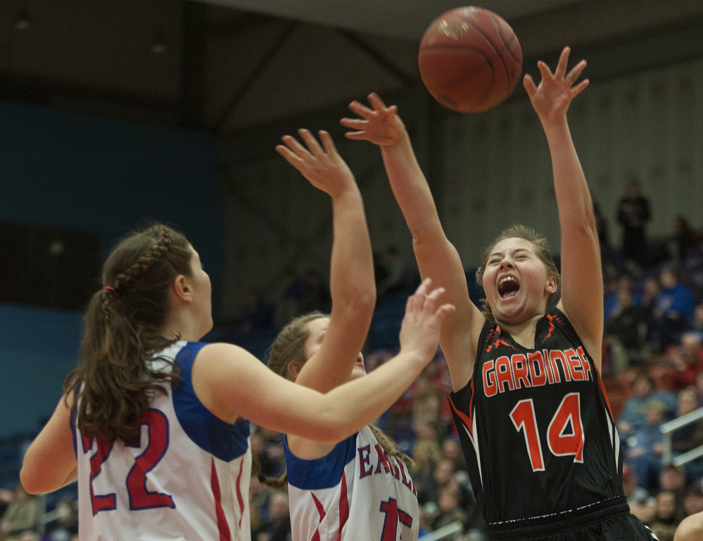 Gardiner's Logan Granholm throws up a shot as Messalonskee's Makayla Wilson and McKenna Brodeur defend during a Class A North quarterfinal game Friday at the Augusta Civic Center.