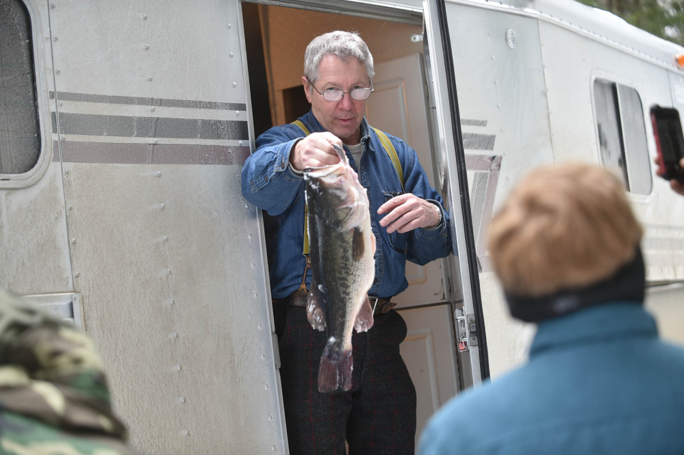 Tom Bolon holds a 5-pound bass caught Saturday by Chris Lee during the Albion Lions Club-sponsored fifth annual Ice Fishing Derby on Lovejoy Pond in Albion.