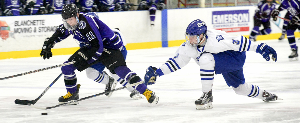 Lewiston's Ryan Bossie attempts to slide in under Waterville's Jackson Aldrich to nab control of the puck in the first period of a game Tuesday at the Androscoggin Bank Colisee in Lewiston.