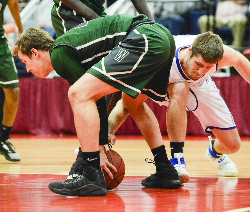 Madison's Mitch Jarvais attempts to recover the ball from Waynflete's Christian Brooks during the first quarter of a Class C South semifinal Thursday at the Augusta Civic Center.