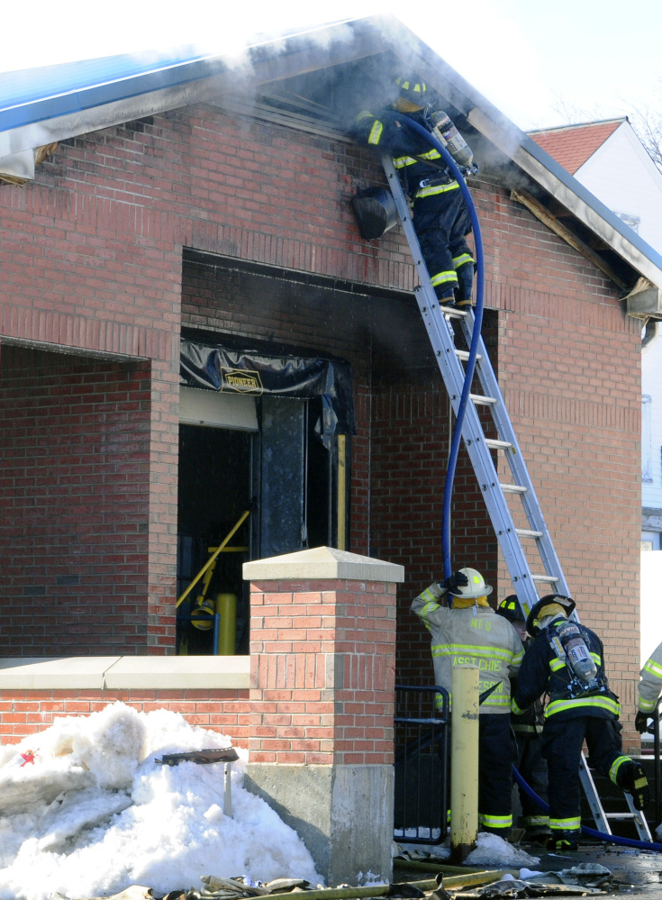Firefighters work last week at the Winthrop post office, where federal officials have determined a fire probably was the result of a mechanical or electrical malfunction.