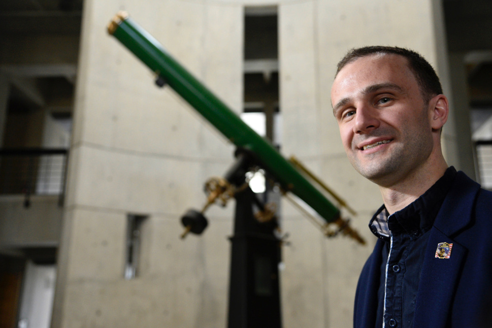 "Kirby Runyon, a Johns Hopkins University Ph.D. candidate in planetary geology, is lead author on a conference abstract that gives a geophysical definition for ""planet."" In background is the Hastings Refractor in the Bloomberg Center for Physics and Astronomy."