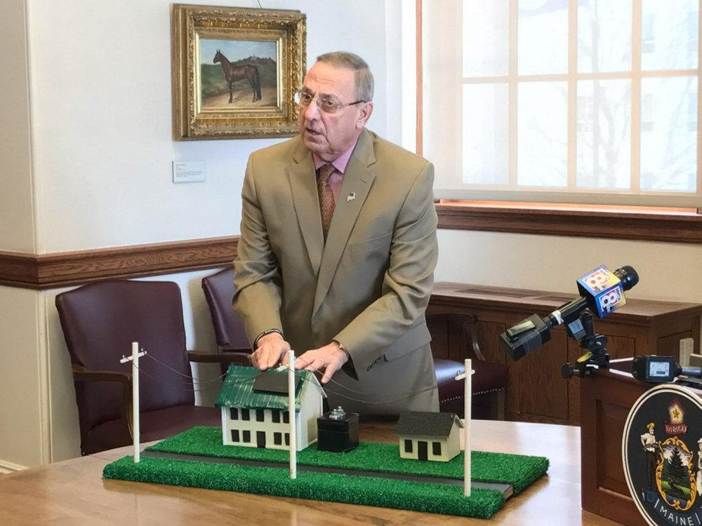 Gov. Paul LePage uses a prop model of two houses to make a point about residential solar energy use in Augusta.