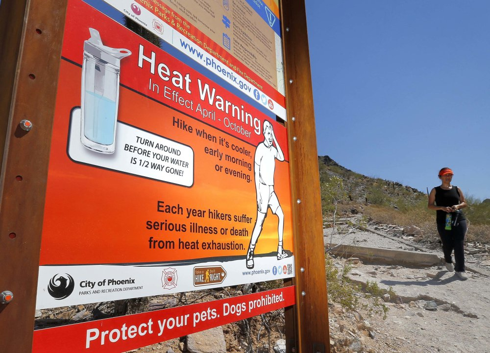 A sign warning of extreme heat is seen on a trailhead at Piestewa Peak in Phoenix, Ariz., in 2016. Phoenix is one of many U.S. cities facing what seems to be the inevitable reality of a hotter and drier future. Public health and economic prosperity are both at risk