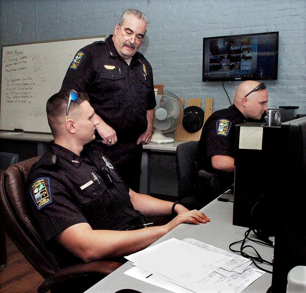 Skowhegan Police Chief Don Bolduc, center, oversees officers C.J. Vera, left, and Ian Shalit filling out police reports at the department on June 15, 2016.