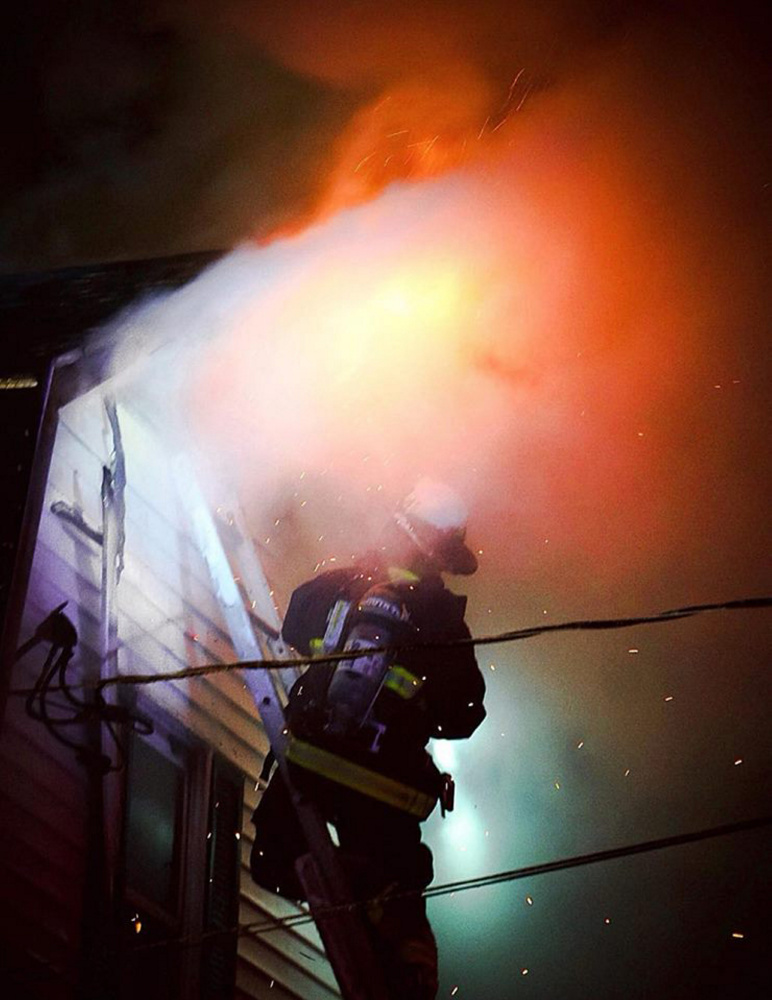 Monmouth firefighter Josh Reny fights the fire that broke out Tuesday night in a home on Route 135 in Monmouth.