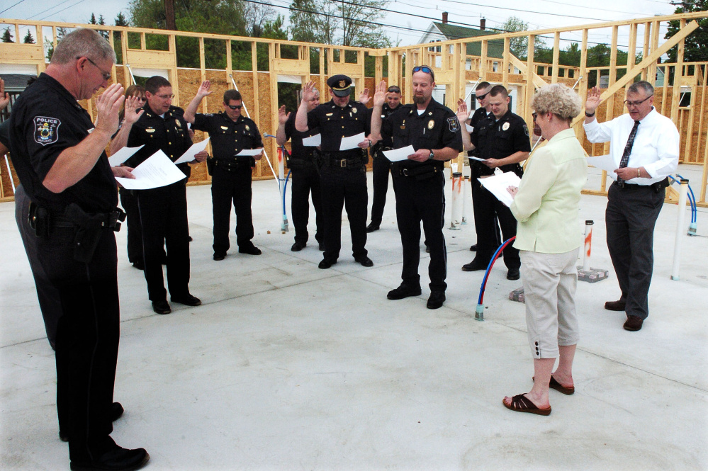 Oakland Town Clerk Jan Porter swears in Oakland police officers and Town Manager Gary Bowman, at right, on May 25, 2016, inside the construction zone of the town's new police station. Oakland police officers voted Friday to unionize with the Maine Association of Police.
