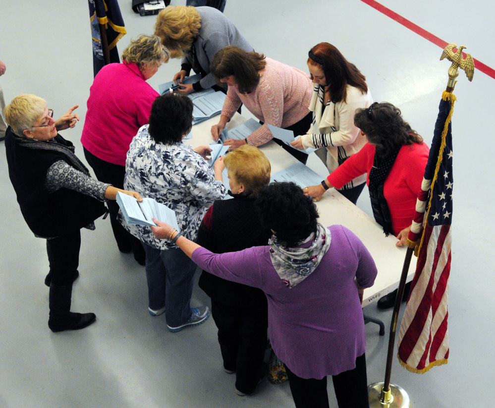 Officials sort and count ballots from morning voting Saturday in West Gardiner's fire station before the West Gardiner Town Meeting.
