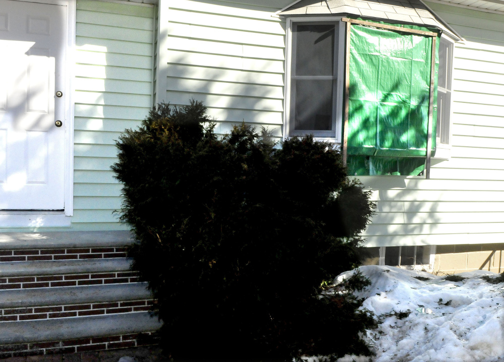 A tarpaulin covers a broken front window March 13 at the Audrey Hewett residence at 47 Lyons Road in Sidney. Police say Dreaquan Foster, 21, of Rhode Island, was shot in the chest there by Hewett's son after a fight.