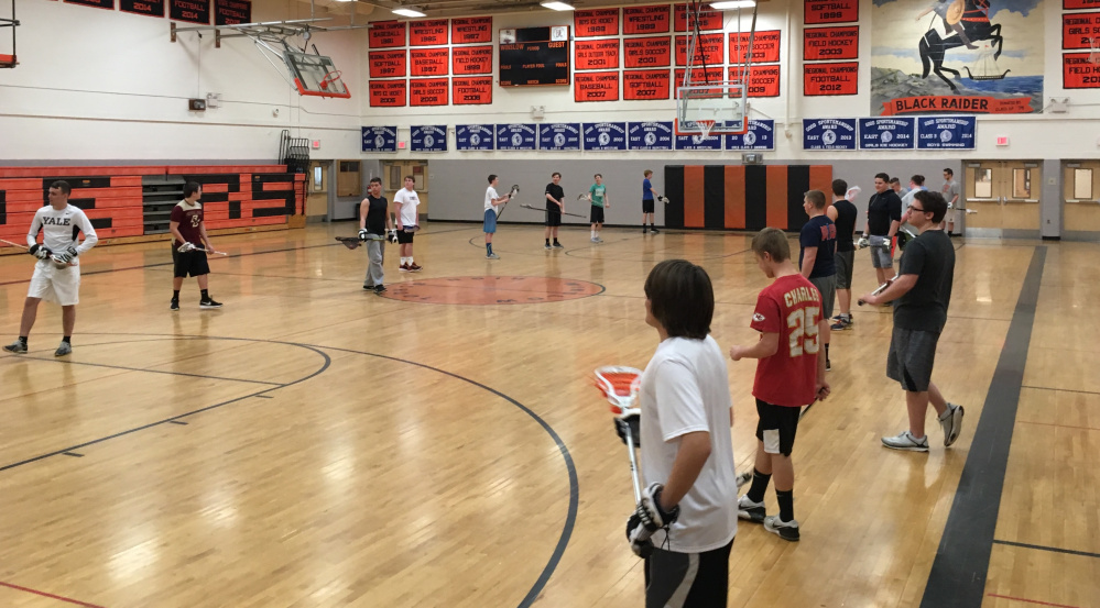 Members of the Winslow boys lacrosse team practice Monday inside the high school gymnasium.