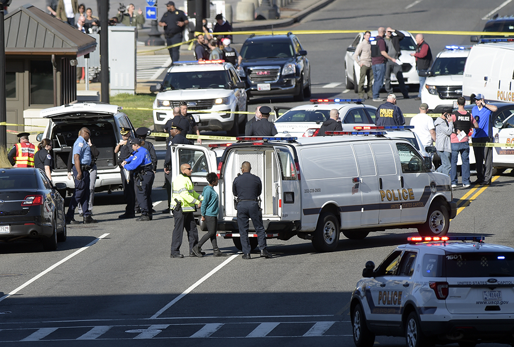 A woman, center, is taken into custody on Capitol Hill Wednesday, after police say she  struck a Capitol Police cruiser.