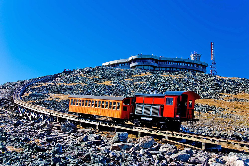 A Mount Washington Cog Railway locomotive pushes a car to the summit of the highest peak in the Northeast. The railway's owner wants to build an upscale hotel about a mile below that the train would pass through on its way to and from the summit. Photo courtesy of Mount Washington Cog Railway