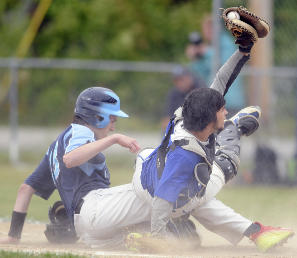 Hanging on: Erskine catcher Nick Turcotte holds onto the ball for the out as Oceanside's Michael Norton slides home during a Class B North quarterfinal game last season in South China.
