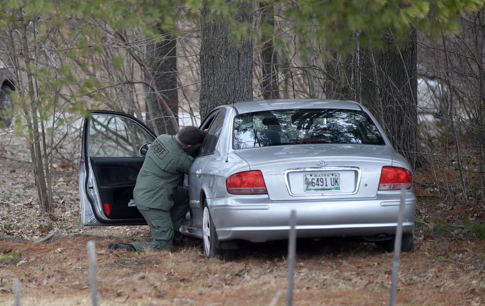 Detective Sgt. Scott Mills, of the Kennebec County Sheriff's Office, investigates a car crash Thursday on Mayflower Hill Drive at Colby College in Waterville. The driver, Donovan M. Gray. 68. died later in a hospital.