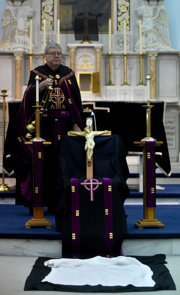 Father Larry Jensen holds the figure of Jesus used in the Good Friday rite where communicants kiss the feet at St. Joseph's Maronite Church in Waterville on April 14. Jensen has been relieved of his priestly duties amid allegations of sexual abuse 15 years ago in Connecticut.