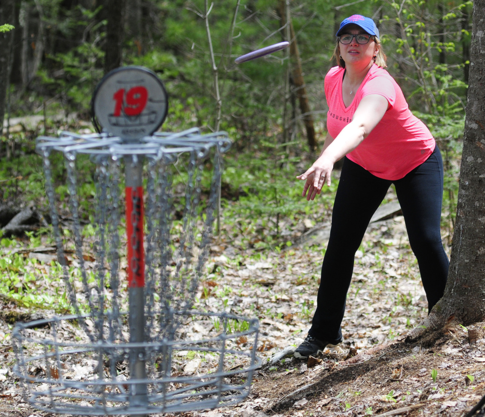 Staff photo by Joe Phelan   Megan Norton throws her disc toward the basket on Saturday during the Farmers Daughters Open at CR Farm Disc Golf in West Gardiner.