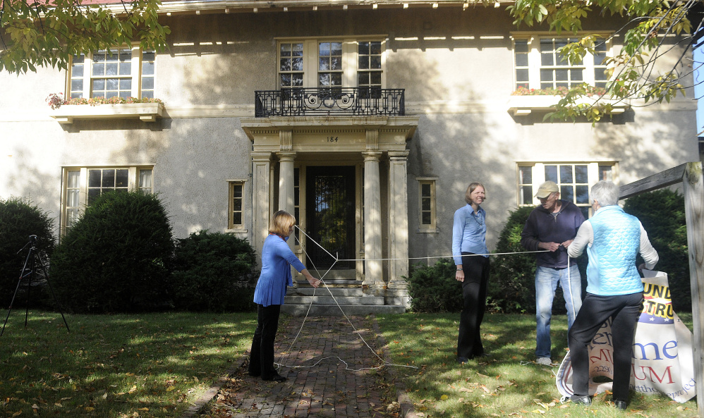 Genie Gannett, left, unknots a rope that Rebecca Lazure, second from left, Denis Thoet and Susan Gross used to hang a sign for the First Amendment Museum in front of the Gannett House in Augusta in this October 3 file photo. Gannett serves as chairwoman and president of the board; Lazure serves as executive director and Gross and Thoet are on the board.