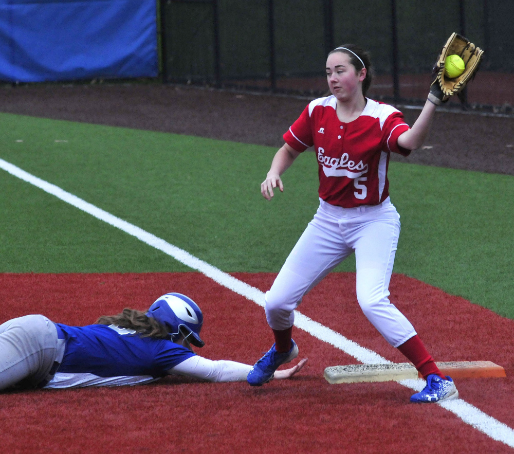 Lawrence runner Haley Holt slides safely back into first base as Messalonskee's Alyssa Genness takes the throw during a Kennebec Valley Athletic Conference Class A game Monday at Colby College in Waterville.