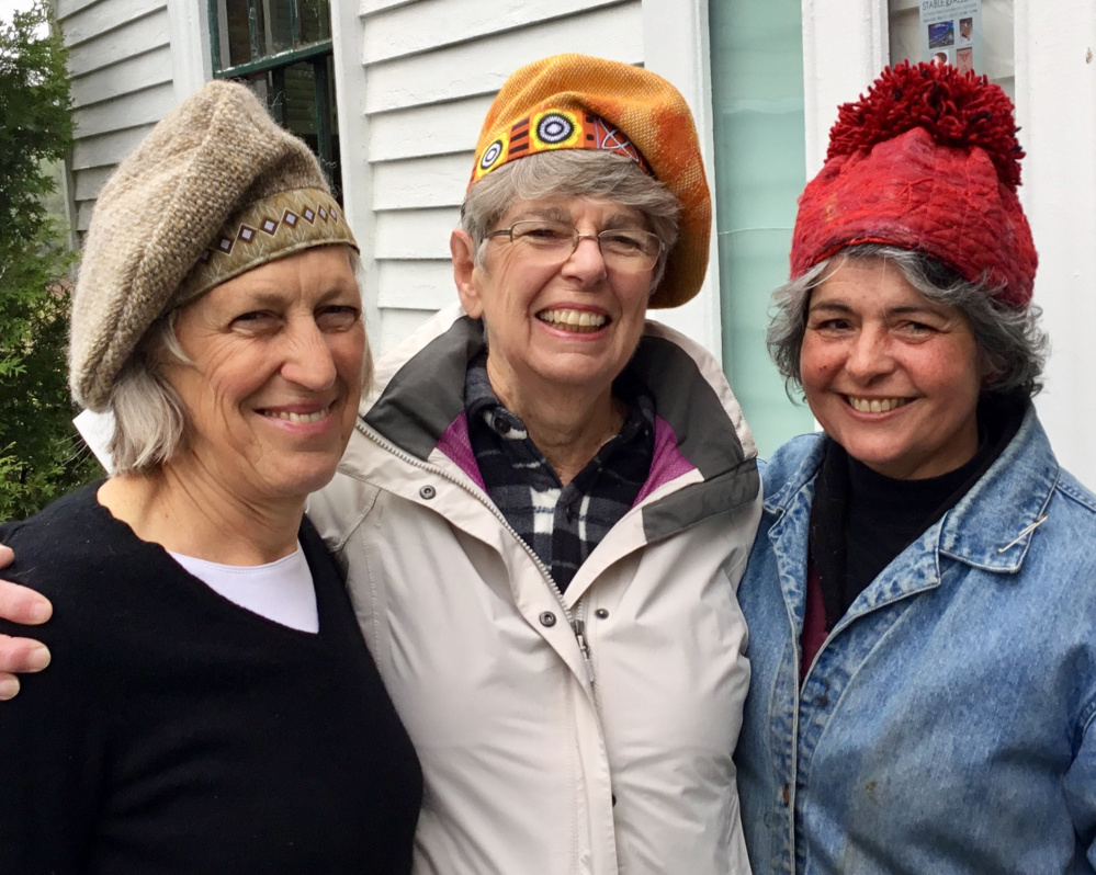 """Stable Gallery artists, from left, Polly Smith, Mary Hall and Roz Welsh model hats created by Susan Perrine""""."""