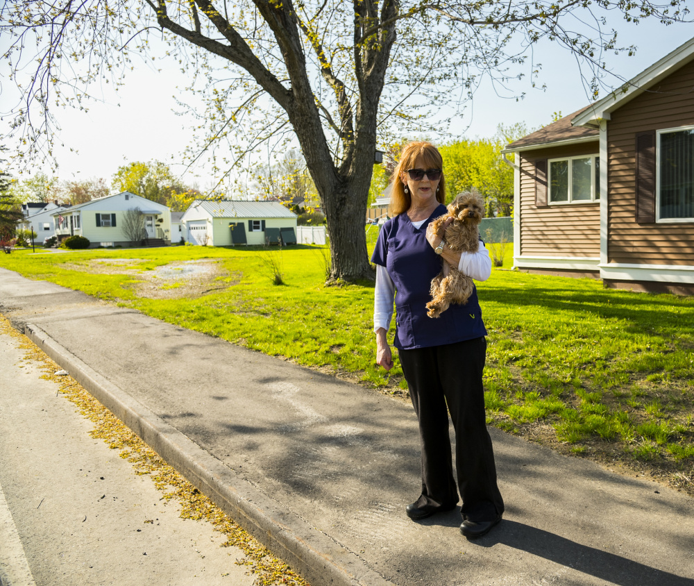 Jacquelyn Cyr of Windsor Avenue in Augusta stands with her dog Poppy on Wednesday on a new sidewalk in front of her house. She said that the sidewalk, which was replaced two years ago, is causing standing water on lawns in her neighborhood.