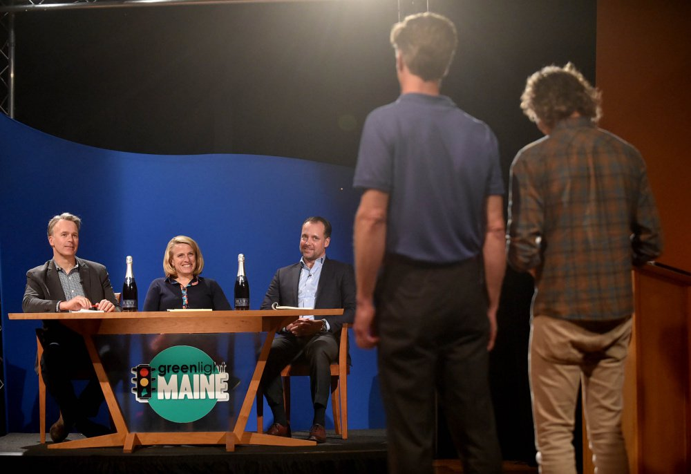"""""""Greenlight Maine"""" judges, from left, Michael Burgmaie of Whipstitch, Betsy Peters, chief revenue officer at Better Lessons, and Michael Petit of JMH Capital listen to a business pitch Tuesday from Bluet sparkling blueberry wine owners Eric Martin, far right, and Michael Terrien, second from left in foreground, during the recording of """"Greenlight Maine"""" at Thomas College in Waterville."""