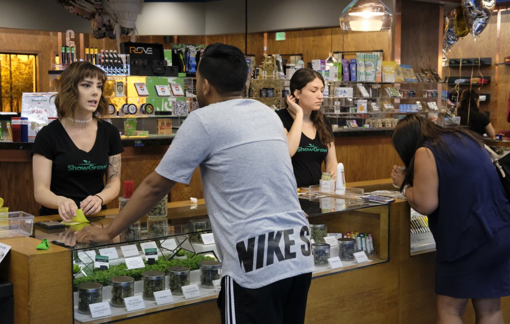 Bud tenders assist customers at a Los Angeles medical pot dispensary. State officials hope to begin issuing licenses in January to businesses in the legalized recreational market.