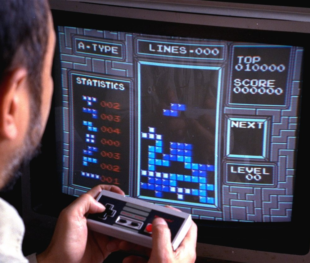 """A Nintendo gamer plays """"Tetris"""" in this photo from June 1990. This weekend, audiences will pack a concert hall in Paris to hear the London Symphony Orchestra performing videogame music."""